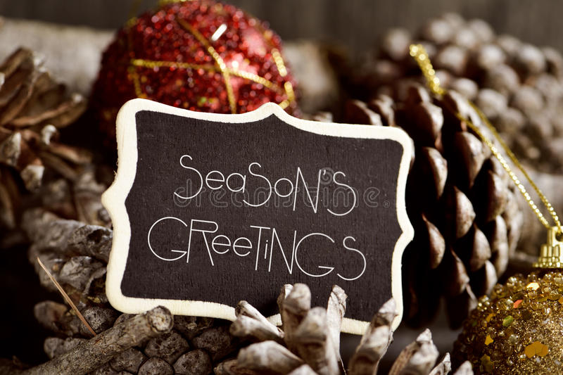 Text seasons greetings, pine cones and baubles. The text seasons greetings written in a black signboard and some pine cones and christmas balls stock image