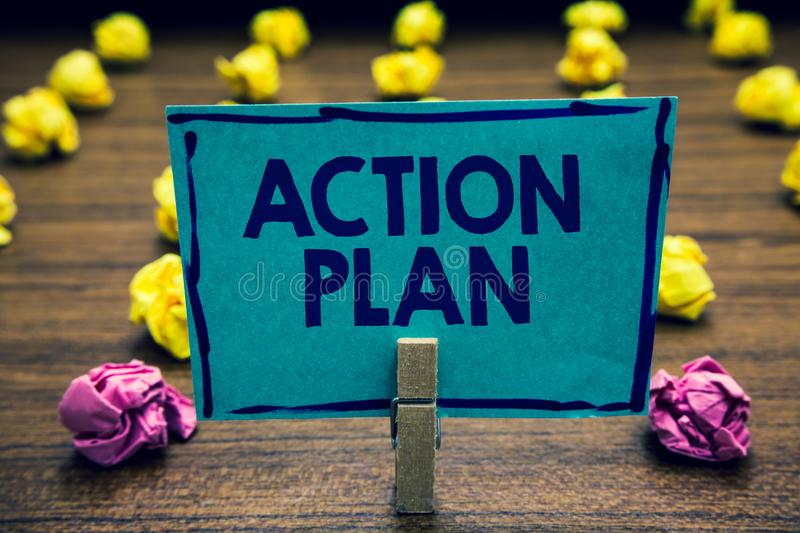 Text sign showing Action Plan. Conceptual photo list of things or schedule to be made thia current year Clothespin holding blue pa. Per note crumpled papers stock photo