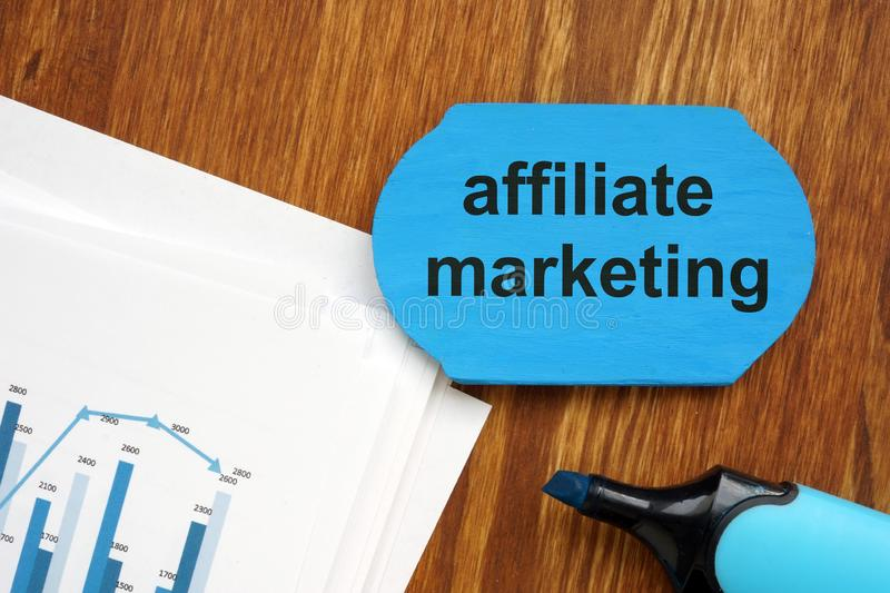Text sign showing affiliate marketing. The text is written on a small wooden board. Graphs on the paper sheet, markers, wooden royalty free stock images