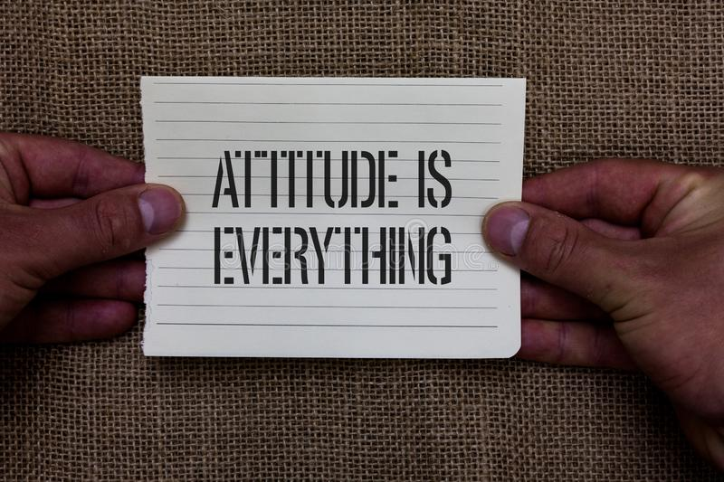 Text sign showing Attitude Is Everything. Conceptual photo Positive Outlook is the Guide to a Good Life Man holding piece notebook. Paper jute background royalty free stock images