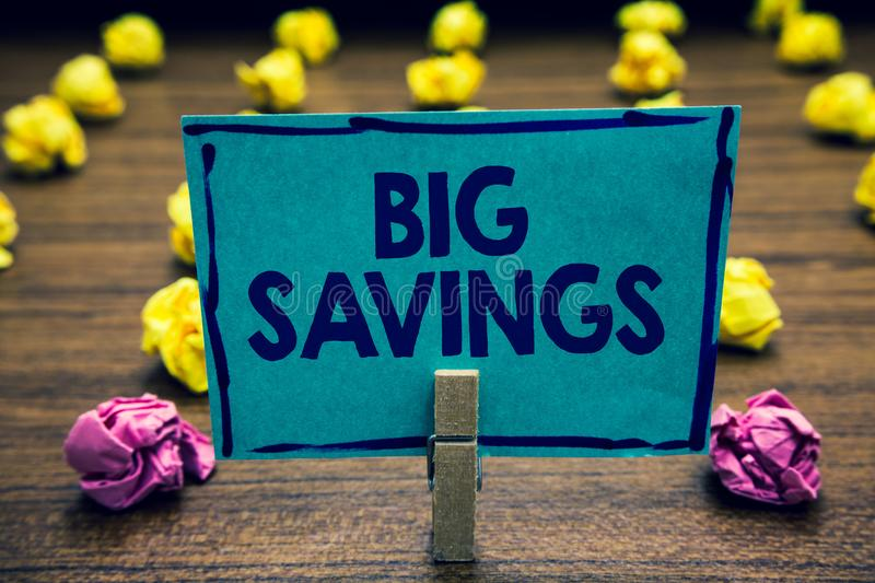 Text sign showing Big Savings. Conceptual photo income not spent or deferred consumption putting money aside Clothespin holding bl. Ue paper note crumpled papers stock images