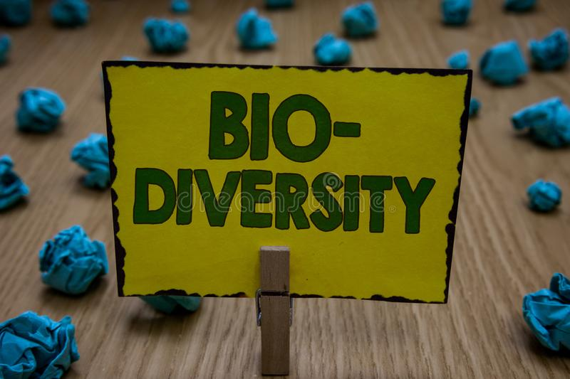 Text sign showing Bio Diversity. Conceptual photo Variety of Life Organisms Marine Fauna Ecosystem Habitat Clothespin. Holding yellow paper note crumpled papers royalty free stock photos