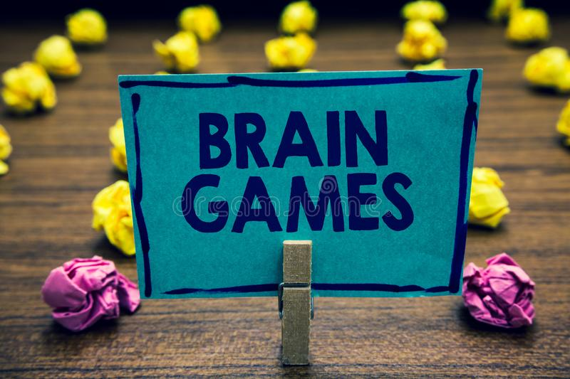 Text sign showing Brain Games. Conceptual photo psychological tactic to manipulate or intimidate with opponent Clothespin holding. Blue paper note crumpled royalty free stock image