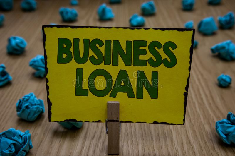Text sign showing Business Loan. Conceptual photo Credit Mortgage Financial Assistance Cash Advances Debt Clothespin holding yello. W paper note crumpled papers royalty free stock images