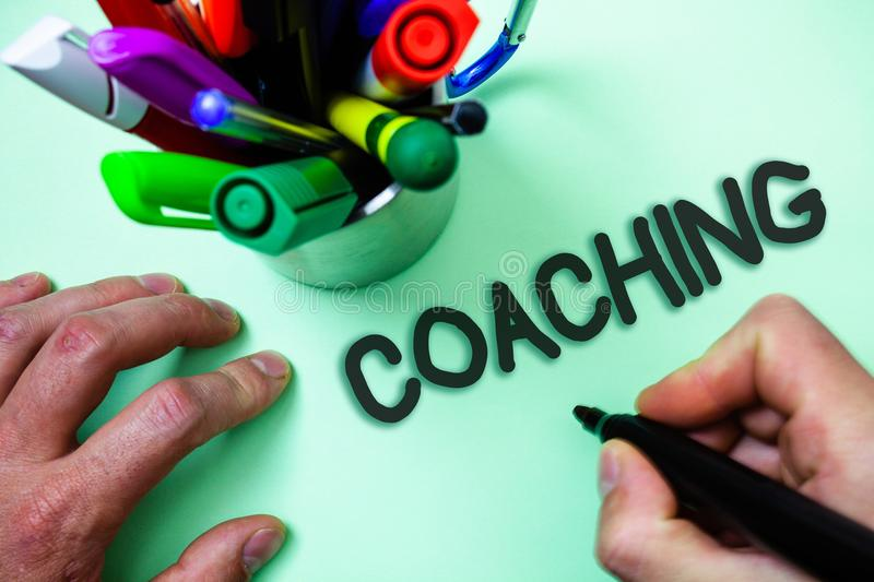 Text sign showing Coaching. Conceptual photo Prepare Enlightened Cultivate Sharpening Encourage Strenghten Man holding black marke. R white background markers royalty free stock photo