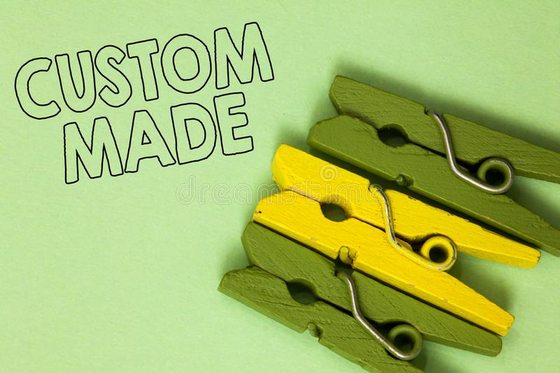 Text sign showing Custom Made. Conceptual photo something is done to order for particular customer organization Three green yellow. Vintage clothespins clear royalty free stock photo