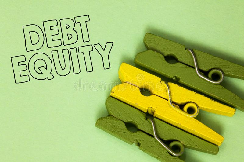 Text sign showing Debt Equity. Conceptual photo dividing companys total liabilities by its stockholders Three green yellow vintage. Clothespins clear background stock images