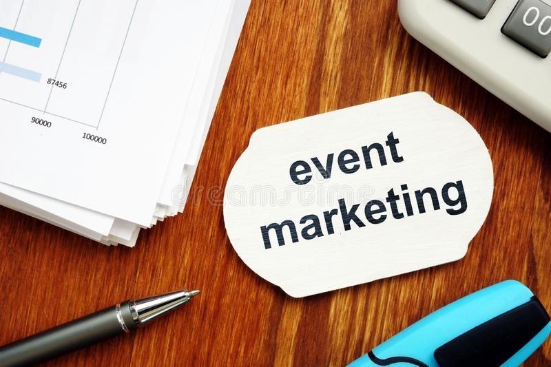 Text sign showing event marketing. The text is written on a small wooden board. Graphs on the paper sheet, pen, keyboard, wooden stock photo