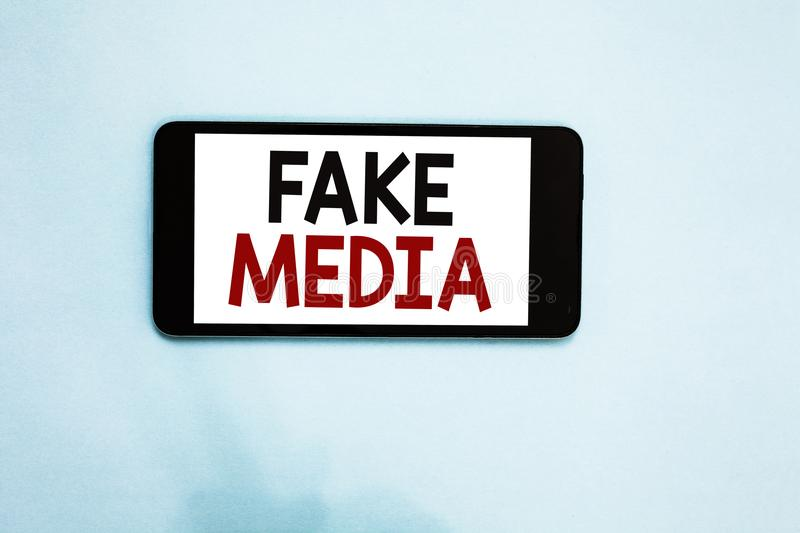 Text sign showing Fake Media. Conceptual photo An formation held by brodcasters which we cannot rely on Cell phone white screen ov. Er light blue background text royalty free stock photos