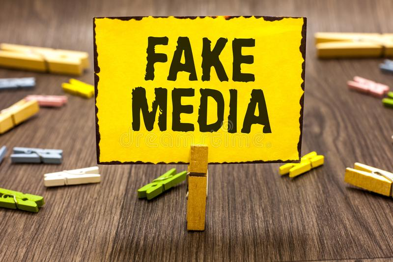 Text sign showing Fake Media. Conceptual photo An formation held by brodcasters which we cannot rely on Clothespin holding yellow. Paper note several royalty free stock image