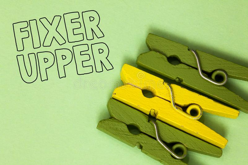 Text sign showing Fixer Upper. Conceptual photo house in need of repairs used chiefly connection with purchase Three green yellow. Vintage clothespins clear royalty free stock photo
