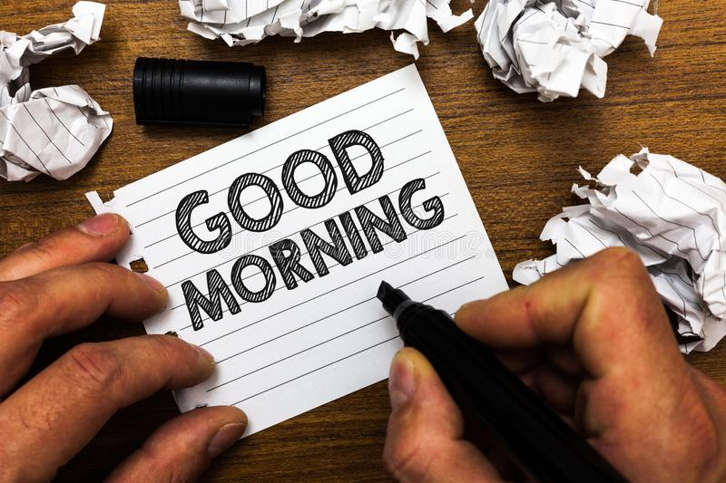 Text sign showing Good Morning. Conceptual photo A conventional expression at meeting or parting in the morning Man holding marker. Notebook page crumpled stock photo