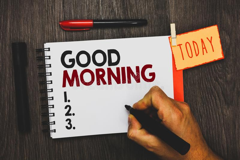 Text sign showing Good Morning. Conceptual photo A conventional expression at meeting or parting in the morning Man holding marker. Notebook clothespin hold stock image