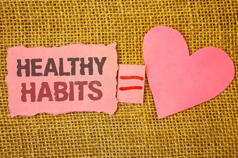 Text sign showing Healthy Habits. Conceptual photo Good nutrition diet take care of oneself Weight Control Text pink torn note equ. Als is pink heart love stock photos