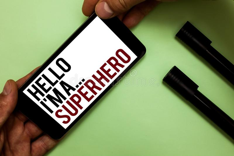 Text sign showing Hello I am A ... Superhero. Conceptual photo Special powers Cartoon character Customs strenght Man's hand hold. IPhone with black and red stock photography