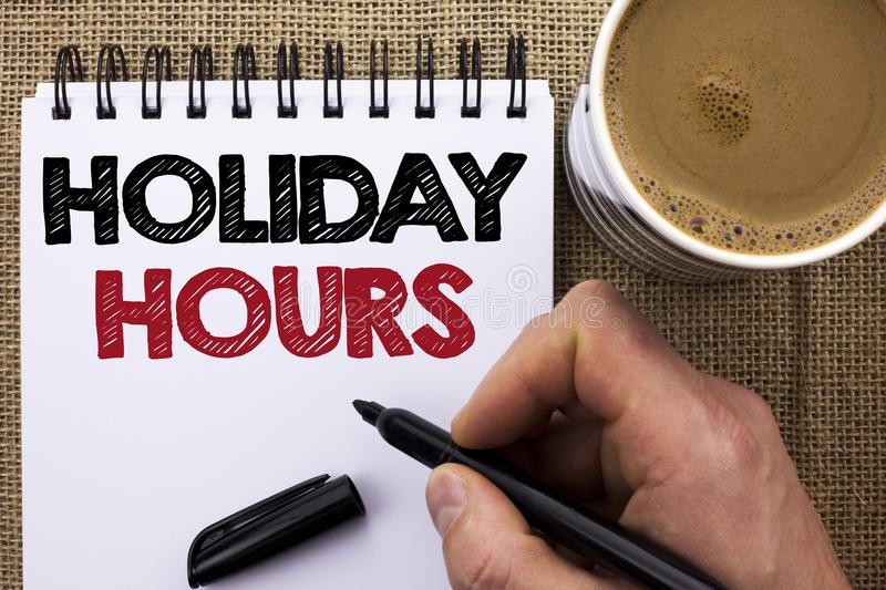 Text sign showing Holiday Hours. Conceptual photo Celebration Time Seasonal Midnight Sales Extra-Time Opening written by Man Holdi. Ng Marker Notebook Book the royalty free stock photo