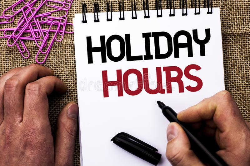 Text sign showing Holiday Hours. Conceptual photo Celebration Time Seasonal Midnight Sales Extra-Time Opening written by Man Holdi. Ng Marker Notebook Book the royalty free stock images