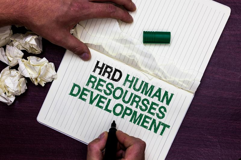 Text sign showing Hrd Human Resources Development. Conceptual photo helping employees develop personal skills Man holding marker n. Otebook page crumpled papers stock photos