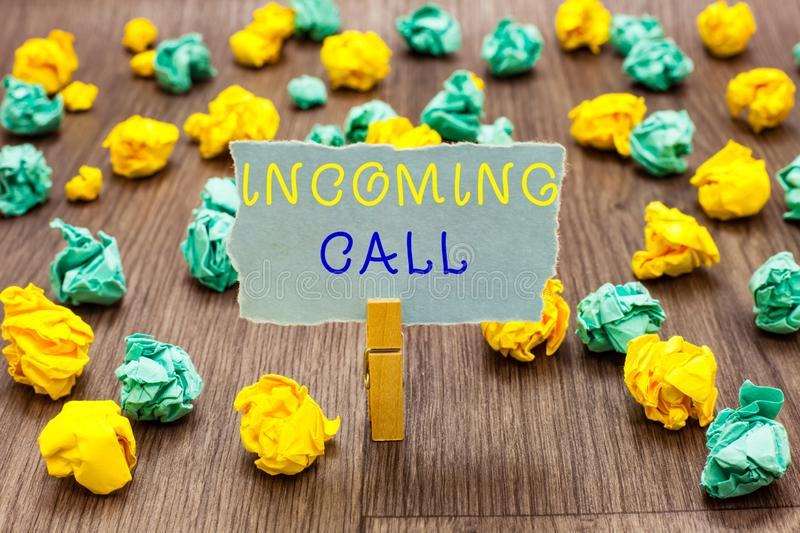 Text sign showing Incoming Call. Conceptual photo Inbound Received Caller ID Telephone Voicemail Vidcall Clothespin. Holding gray note paper crumpled papers royalty free stock images