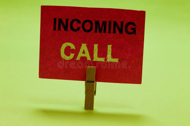 Text sign showing Incoming Call. Conceptual photo Inbound Received Caller ID Telephone Voicemail Vidcall Clothespin. Holding red paper important communicating stock image