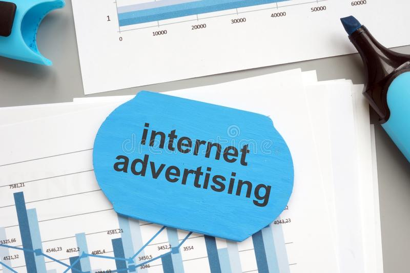 Text sign showing internet advertising. The text is written on a small wooden board. Papers with graphs, Markers, markers, wooden royalty free stock photo