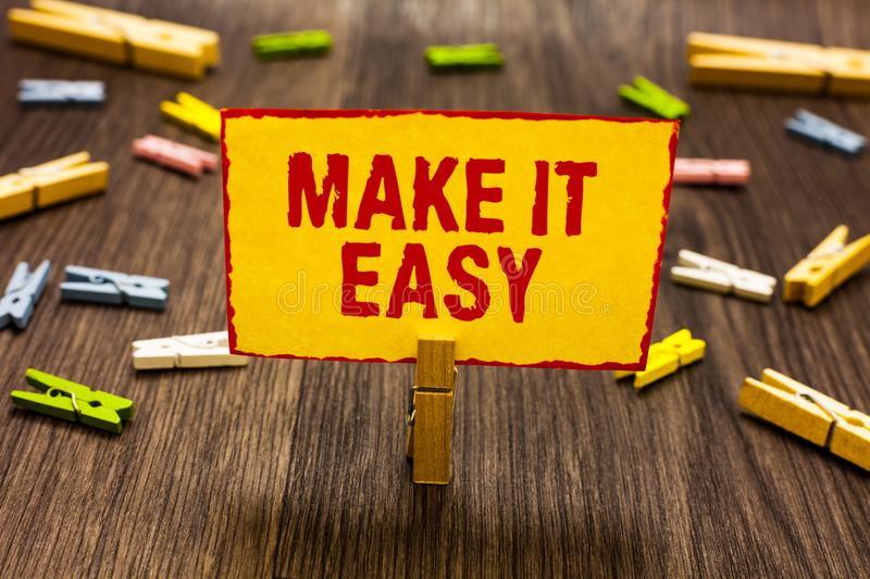 Text sign showing Make It Easy. Conceptual photo Smart approach Effortless Free from worries or difficulties Clothespin holding ye. Llow paper note several stock photography