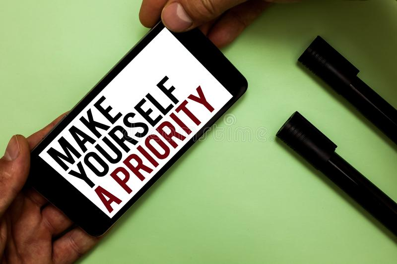 Text sign showing Make Yourself A Priority. Conceptual photo Think in your own good first personal development Man's hand hold iP. Hone with black and red words stock photo