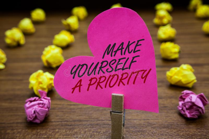 Text sign showing Make Yourself A Priority. Conceptual photo Think in your own good first personal development Paperclip hold pink. Heart with text blurry paper royalty free stock image