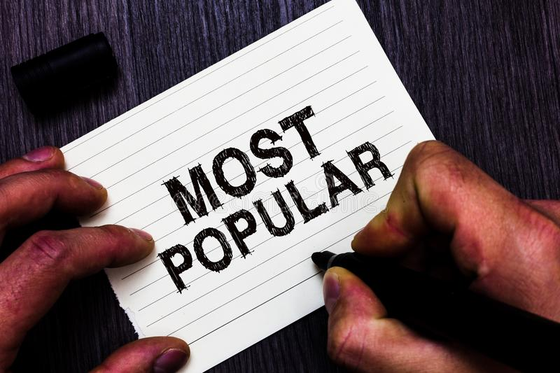 Text sign showing Most Popular. Conceptual photo Liked Followed Enjoyed by majority of the people in a society Man holding marker. Notebook page communicate royalty free stock photo