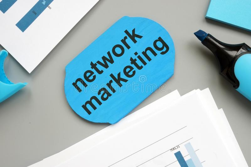 Text sign showing network marketing. The text is written on a small wooden board. Colored paper sheet, markers, wooden background stock image