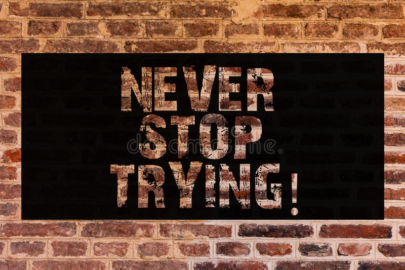 Text sign showing Never Stop Trying. Conceptual photo go on do not give up Self confidence Brick Wall art like Graffiti. Motivational call written on the wall royalty free stock image
