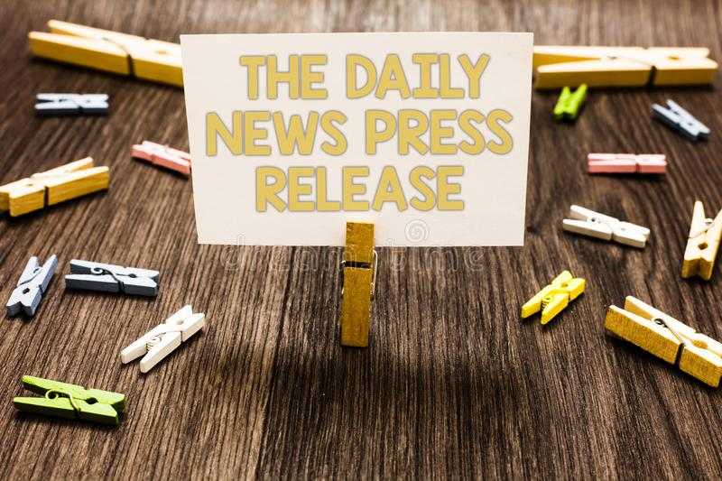 Text sign showing The Daily News Press Release. Conceptual photo announcing big news or speak to people Clothespin holding white p. Aper note several clothespins stock images