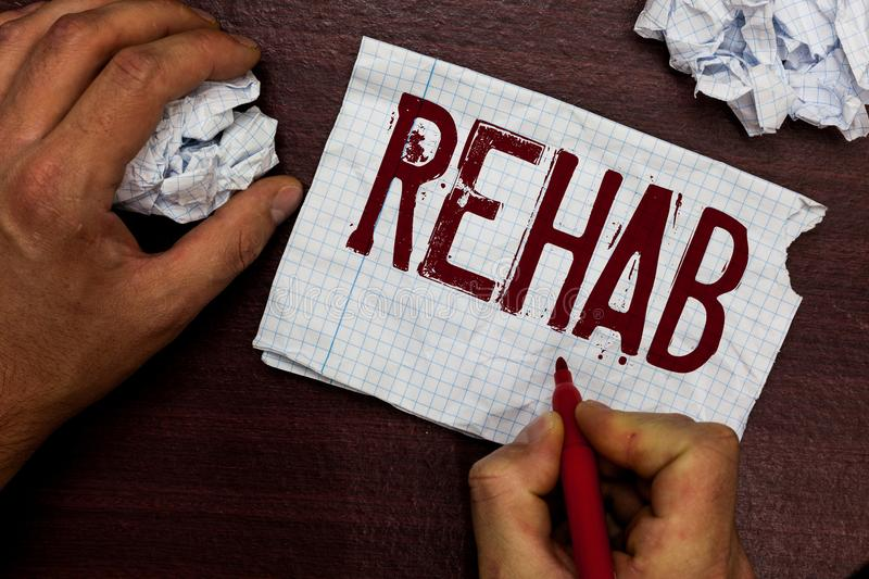 Text sign showing Rehab. Conceptual photo course treatment for drug alcohol dependence typically at residential Man. Holding marker notebook page crumpled stock photo