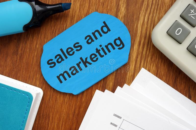 Text sign showing sales and marketing. The text is written on a small wooden board. Papers, Markers, keyboard, wooden background stock photo