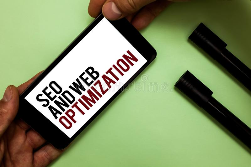 Text sign showing Seo And Web Optimization. Conceptual photo Search Engine Keywording Marketing Strategies Man's hand hold iPhone royalty free stock photos