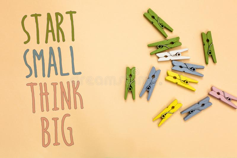 Text sign showing Start Small Think Big. Conceptual photo Initiate with few things have something great in mind Yellow base with p. Ainted texts colorful paper stock photo