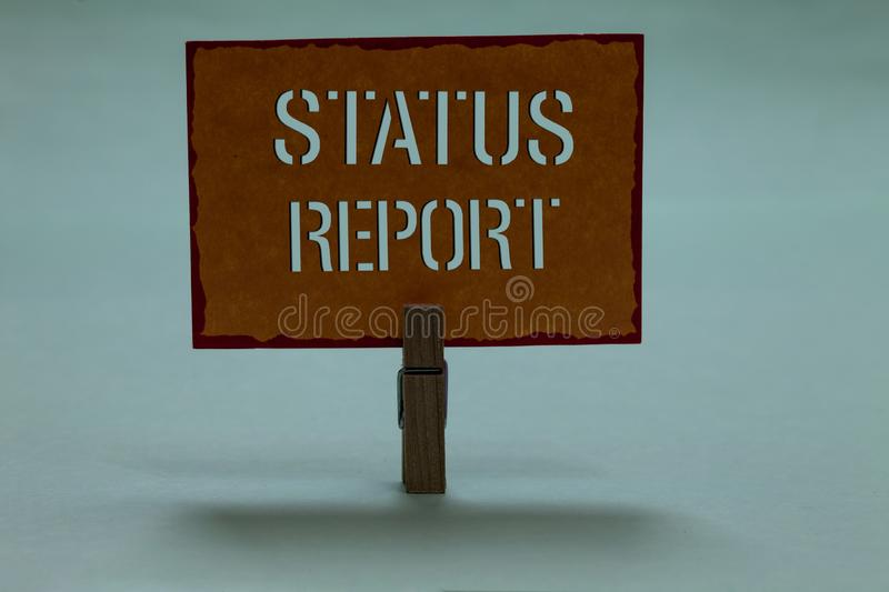 Text sign showing Status Report. Conceptual photo Update Summary of situations as of a period of time Clothespin holding orange pa. Per important communicating stock photos