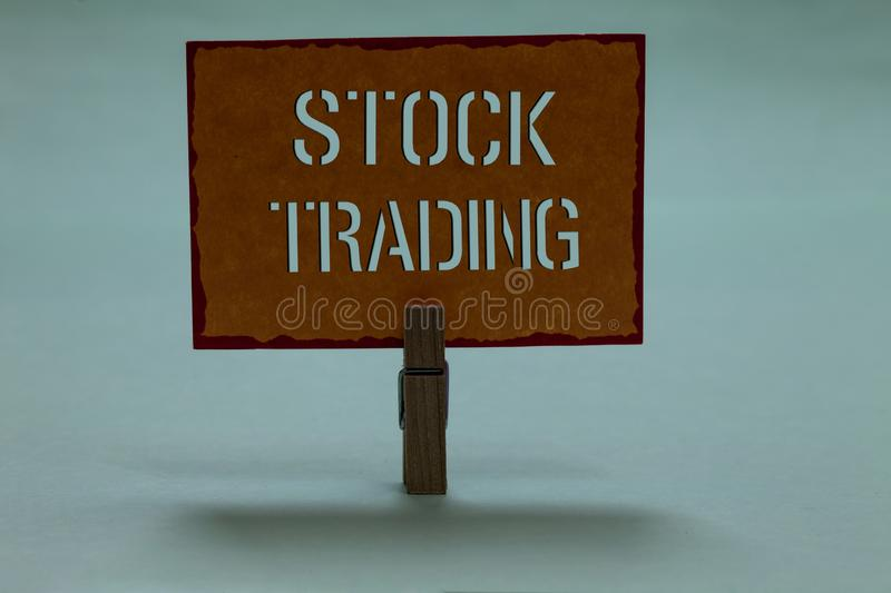 Text sign showing Stock Trading. Conceptual photo Buy and Sell of Securities Electronically on the Exchange Floor Clothespin holdi. Ng orange paper important stock photo