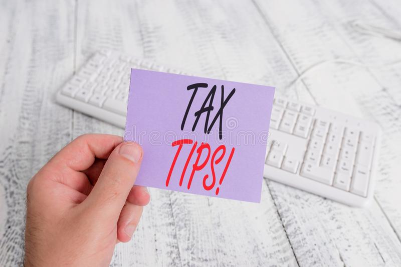 Text sign showing Tax Tips. Conceptual photo compulsory contribution to state revenue levied by government man holding. Text sign showing Tax Tips. Business stock images