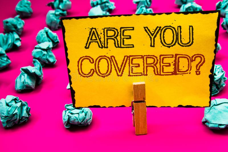 Text sign showing Are You Covered Question. Conceptual photo Have a Security and Health Insurance Medical Care Clothespin hold hol. Ding yellow paper black red stock photos