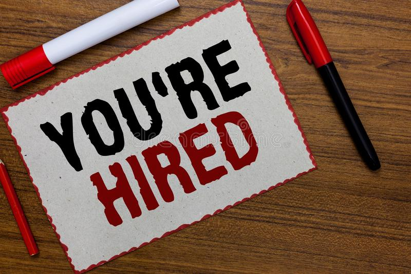 Text sign showing You re are Hired. Conceptual photo New Job Employed Newbie Enlisted Accepted Recruited White paper red borders m. Arkers wooden background royalty free stock photos