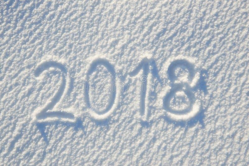 text som 2018 är skriftlig på snö för textur eller bakgrund - begrepp för vinterferie Solig dag ljust ljus med skuggor, lekmanna- royaltyfri foto