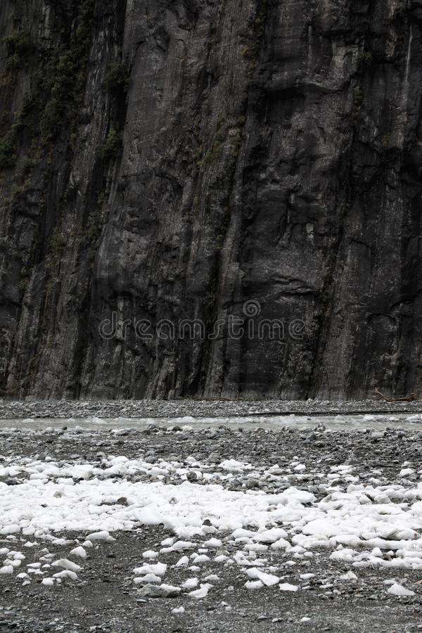 Text space bleak. Dark black rock face rises vertically in front of stones in plain royalty free stock photo