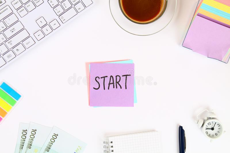 Text Start on the sticker note on the white desktop next to the coffee mug and the keyboard. Top view, flat layout. Text Start on the sticker note on the white royalty free stock photography