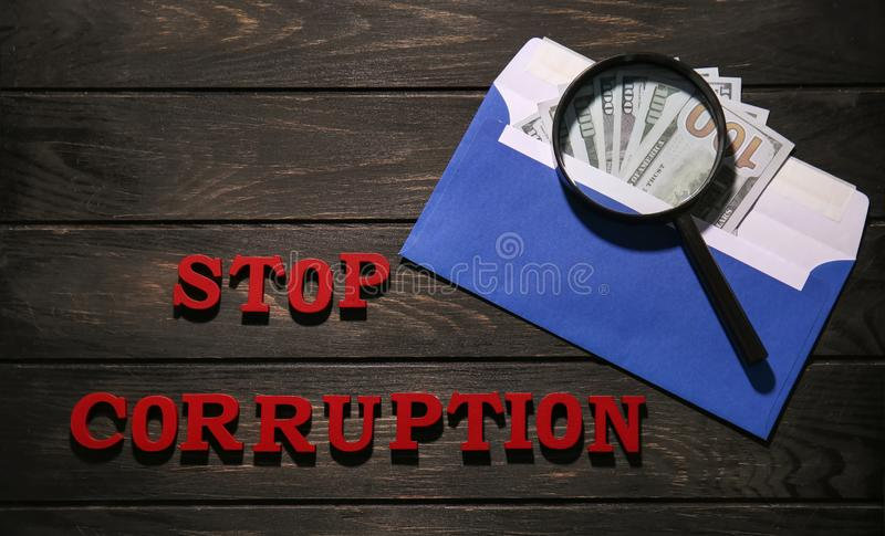 Text STOP CORRUPTION with money and magnifier glass on wooden background stock photo