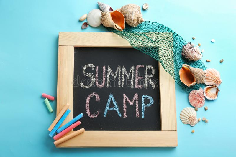 Text Summer Camp on blackboard, colorful chalk and shells, top view royalty free stock photo