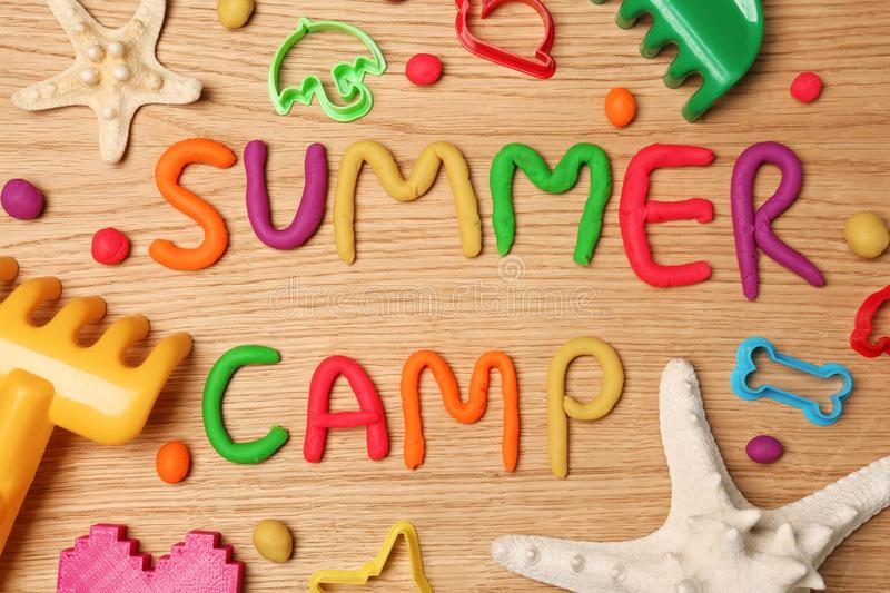 Text SUMMER CAMP made with play dough. On wooden background, top view stock photography