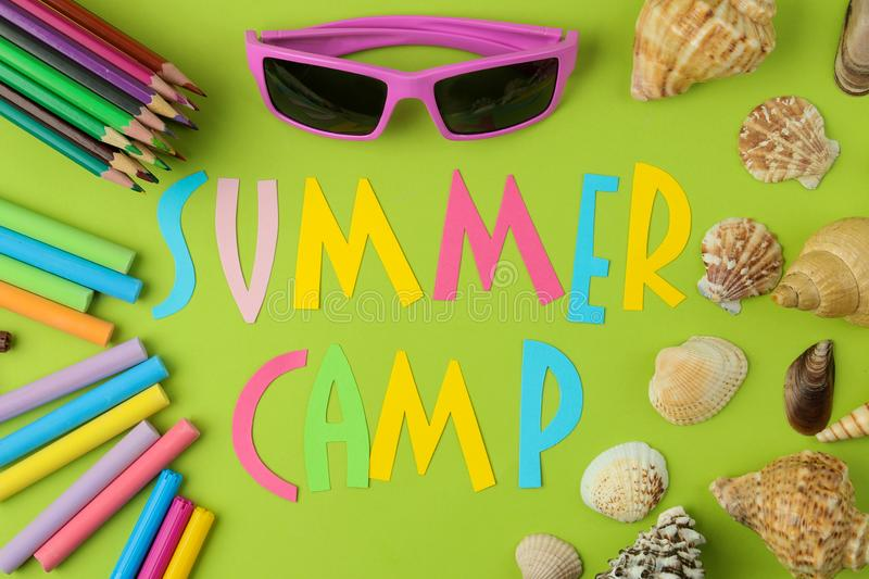 Text SUMMER CAMP of multicolored paper letters and crayons, pencils and seashells on a bright green background. top view. flat lay. Text SUMMER CAMP of royalty free stock photography