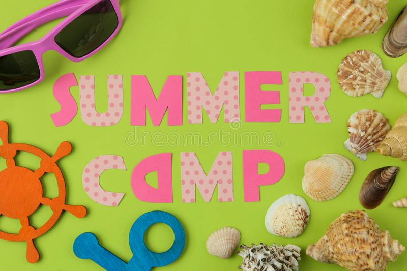 Text SUMMER CAMP of multicolored paper letters and seashells and decorative steering wheel on a bright green background. top view. Flat lay royalty free stock image