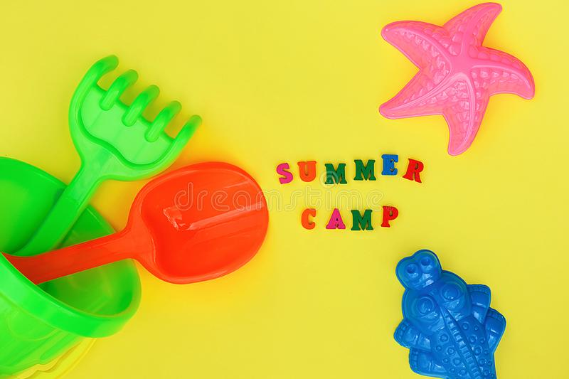 Text Summer camp and multicolored set children`s toys for summer games in sandbox or on sandy beach on yellow background. Creativ stock photography